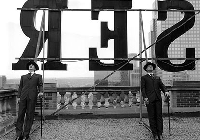 Rodney Smith | COLLIN AND DAVID LEANING ON ROOFTOP LETTERS, ALBERTA, CANADA, 2004